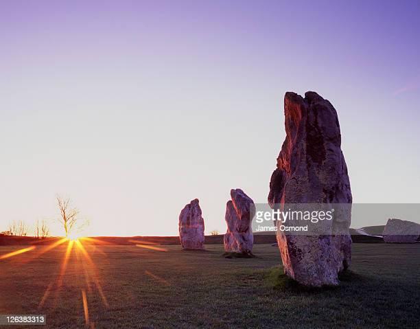 standing stones at avebury at sunrise on the vernal (spring) equinox, designated a unesco world heritage site, the purpose of the ancient obelisks remains an enigma - equinoccio de primavera fotografías e imágenes de stock