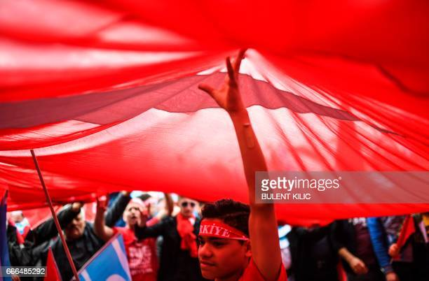 Standing under a huge flag a man listens as the Nationalist Movement Party's leader speak on the stage on April 9 2017 during a campaign rally for...