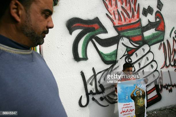 Standing under Palestinian nationalist grafitti a boy carries a campaign poster for the jailed proFatah leader Marwan Barghoutti for the Palestinian...