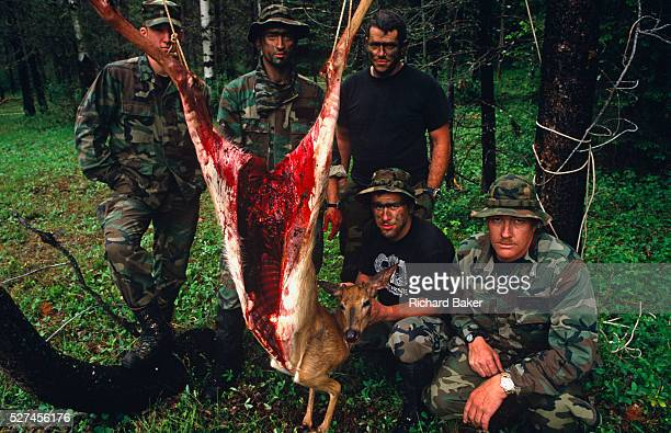 Standing with a recentlykilled deer runover on a nearby highway members of a special US Air Force survival course pose by the gutted carcass of their...