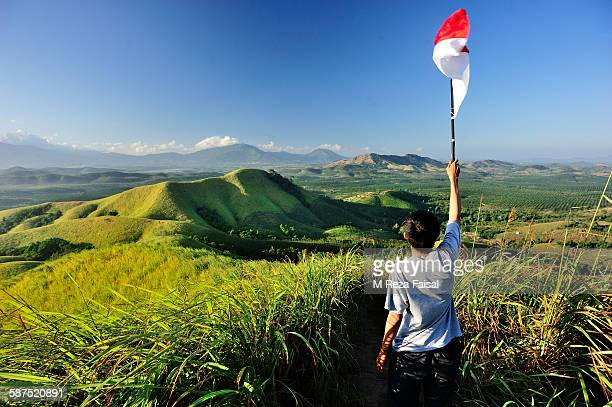 standing with indonesia flag on telang valley - indonesia flag stock photos and pictures