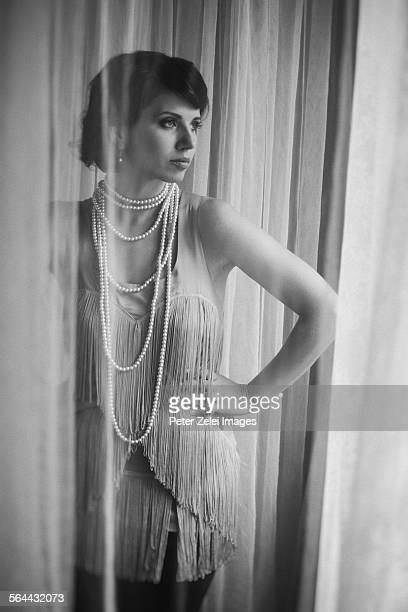 Standing woman between the curtains