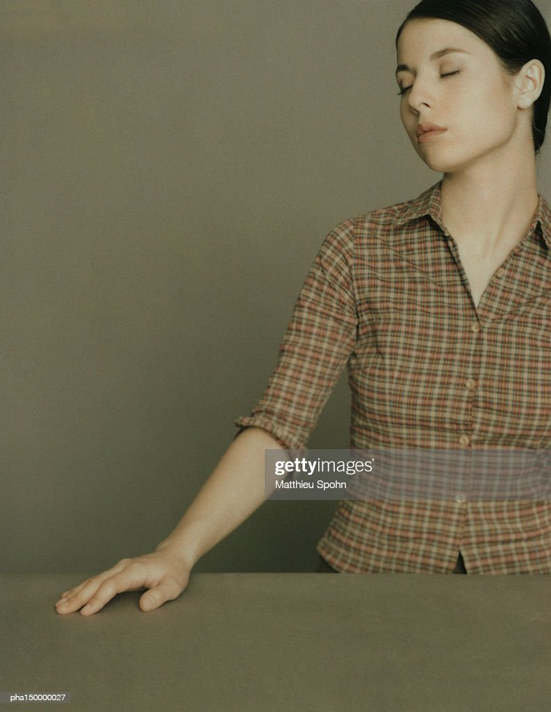 Standing woman, eyes closed, right hand on table facing right, portrait : Stockfoto