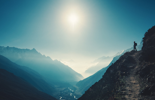 Standing woman on the hill against mountain valley at bright sunny day. Landscape with girl, trail, mountain, blue sky with sun and low clouds at sunset in Nepal.  Lifestyle, travel. Trekking 917911572