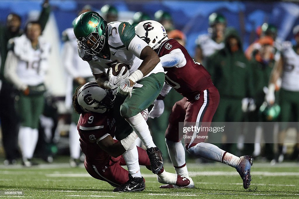 Standish Dobard #5 of the Miami Hurricanes breaks a tackle by Sharrod Golightly #9 of the South Carolina Gamecocks during the fourth quarter of the Duck Commander Independence Bowl at Independence Stadium on December 27, 2014 in Shreveport, Louisiana.
