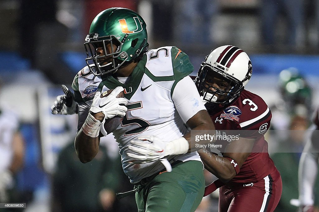 Standish Dobard #5 of the Miami Hurricanes is pursued by Chris Lammons #3 of the South Carolina Gamecocks during the fourth quarter of the Duck Commander Independence Bowl at Independence Stadium on December 27, 2014 in Shreveport, Louisiana.