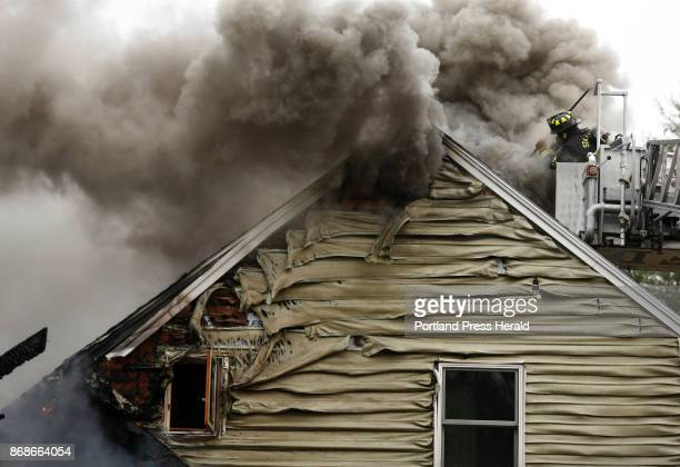 Standish firefighter Alex DeWitt opens a hole in the roof of a house on fire on Middle Road in Standish on Monday Standish Fire Chief Rob Caron said...