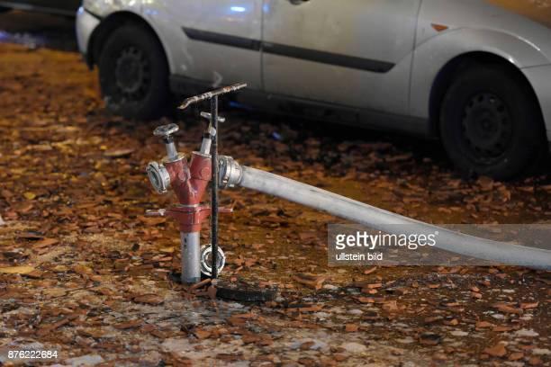 Standrohr in einem Hydranten auf einem mit heruntergefallenen Dachziegeln übersähten Gehweg Löscharbeiten während eines Dachstuhlbrandes in der...