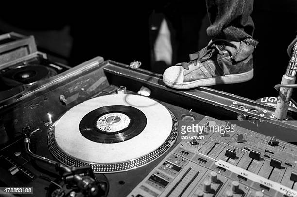 A DJ stands by his turntable at the Glastonbury Festival at Worthy Farm Pilton on June 28 2015 in Glastonbury England Now its 45th year the festival...