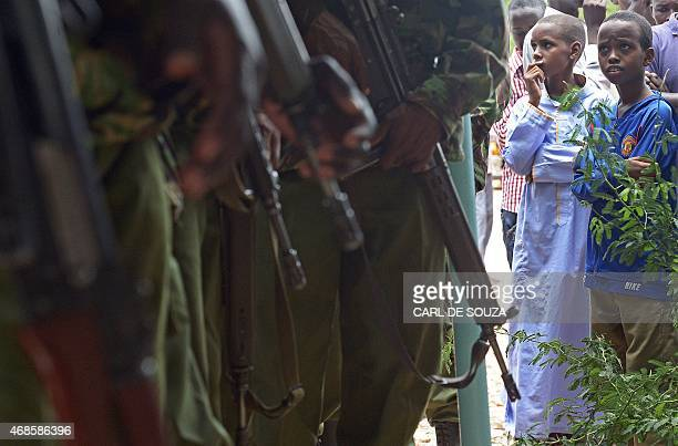 A stands looking at Kenyan Defence Force officers as people gather to view the bodies of the suspected attackers on the Garissa university in the...