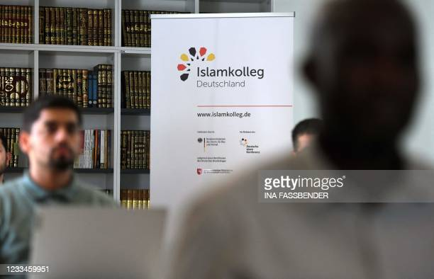 Stand-up display of the Islamkolleg Deutschland is seen in the background as students take part in a Qur'an recitation lesson at the Islamkolleg in...