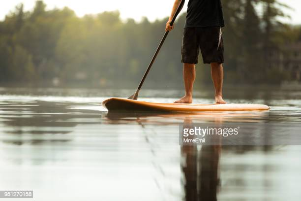 sup stand-up paddleboard. close-up on legs of a man paddleboarding - paddleboard stock photos and pictures