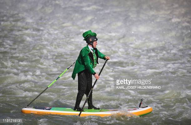 A standup paddler wears a green costume for St Patrick's Day as he paddles on the river Lech in Landsberg am Lech southern Germany on March 17 2019 /...