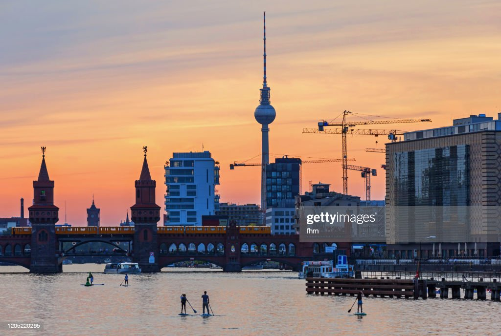 Standup paddlers on Spree river - with Berlin skyline at sunset (Kreuzberg-Friedrichshain, Berlin, Germany) : ストックフォト