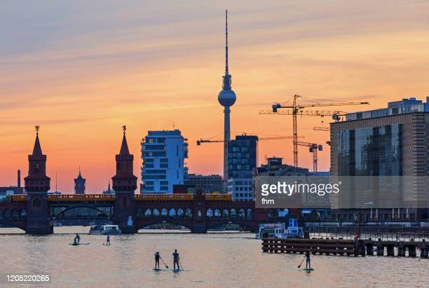 standup paddlers on spree river - with berlin skyline at sunset (kreuzberg-friedrichshain, berlin, germany) - spree river stock pictures, royalty-free photos & images