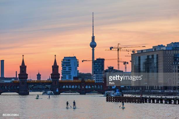 Standup paddlers on Spree river - with Berlin skyline sunset at Oberbaumbrücke and Television-Tower (Kreuzberg-Friedrichshain, Berlin, Germany)