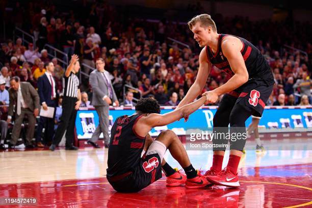 Stanford Cardinal forward James Keefe helps up Stanford Cardinal guard Bryce Wills during a college basketball game between the Stanford Cardinal and...