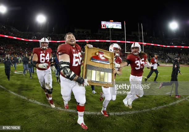 Stanford Cardinal players run on to the field with The Stanford Axe after they beat the California Golden Bears at Stanford Stadium on November 18...