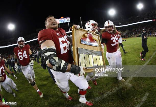 Stanford Cardinal players run on to the field with 'The Stanford Axe' after they beat the California Golden Bears at Stanford Stadium on November 18...