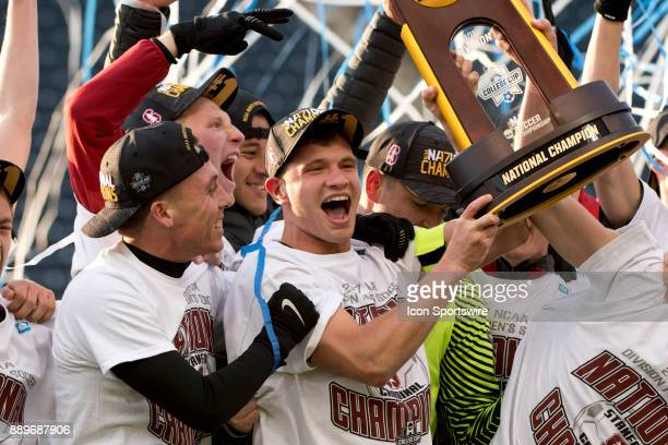 Stanford Defender Tomas HilliardArce holds the Championship Trophy with teammates after winning the College Cup game between The Stanford Cardinal...