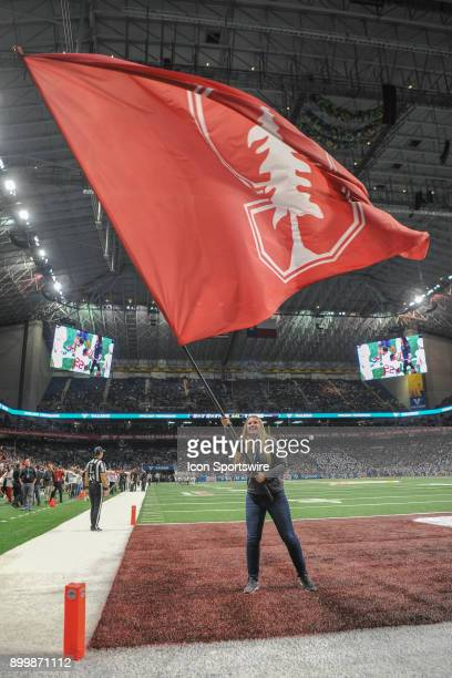 Stanford flag bearer waves the flag in the endzone after a second half touchdown during the Alamo Bowl game between the Stanford Cardinals and the...