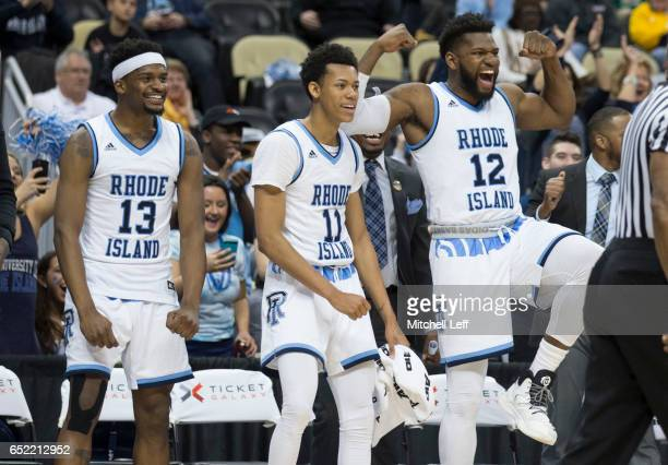 Stanford Robinson Jeff Dowtin and Hassan Martin of the Rhode Island Rams celebrate from the bench against the Davidson Wildcats in the Semifinals of...