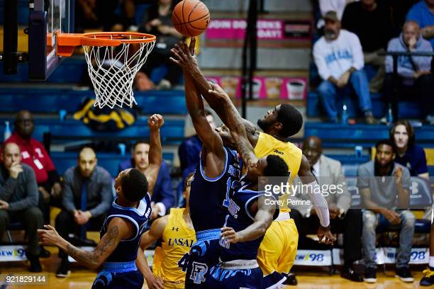 Stanford Robinson of the Rhode Island Rams and BJ Johnson of the La Salle Explorers vie for the ball as Jarvis Garrett of the Rams grabs Johnson's...