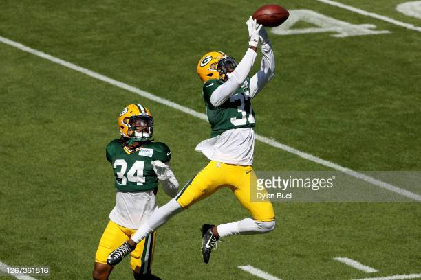 Stanford Samuels and Josh Jackson of the Green Bay Packers participate in a drill during Green Bay Packers Training Camp at Lambeau Field on August...