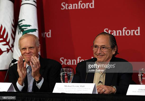 Stanford University president John Hennessy applauds Stanford University School of Medicine biophysicist Michael Levitt during a news conference...