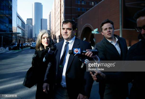 Stanford University sailing coach John Vandemoer center is questioned by reporters as he leaves the John Joseph Moakley United States Courthouse in...