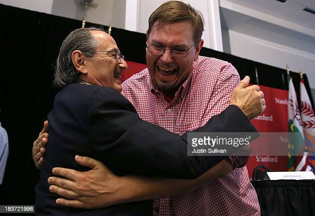 Stanford University School of Medicine biophysicist Michael Levitt is greeted by a friend during a news conference after winning the Nobel Prize in...