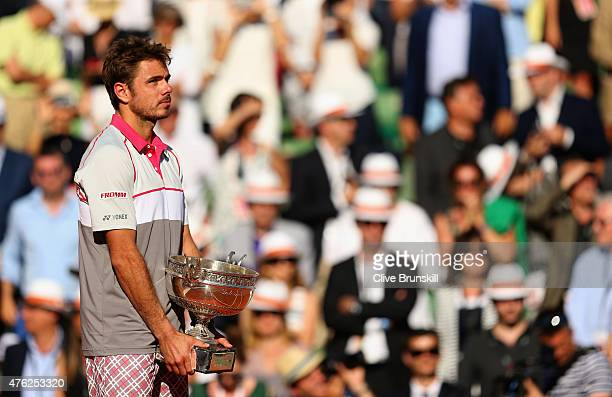 Stanislas Wawrinka of Switzerland lifts the Coupe de Mousquetaires after victory in the Men's Singles Final against Novak Djokovic of Serbia against...
