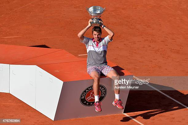 Stanislas Wawrinka of Switzerland poses with the trophy after he won the Men's final match against Novak Djokovic of Serbia on day fifteen of the...