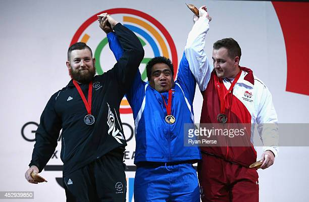 Stanislav Chalaev of New Zealand David Katoatau of Kiribati and Ben Watson of England celebrate with their medals after the Men's Weighlifting 75kg...