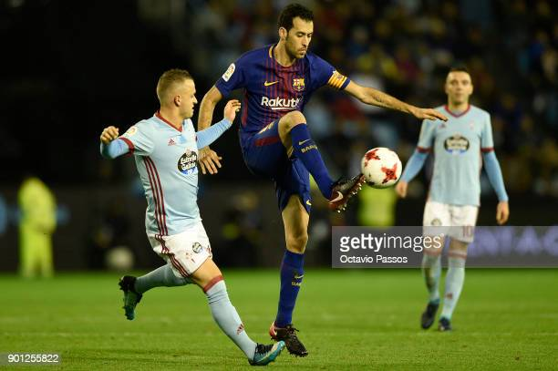 Stanislav Lobotka of RC Celta de Vigo competes for the ball with Sergio Busquets of FC Barcelona during the Copa del Rey round of 16 first leg match...