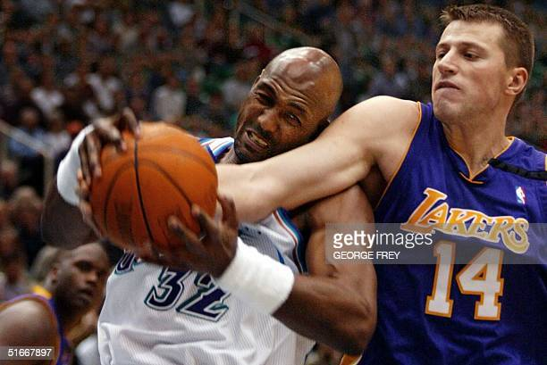 Stanislav Medvedenko of the Los Angeles Lakers fights for a rebound with Karl Malone of the Utah Jazz during the first quarter action 04 December...