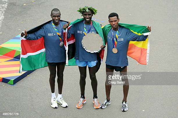 Stanley Biwott of Kenya poses with the first place trophy alongside second place Geoffrey Kipsang Kamworor of Kenya and third place Lelisa Desisa of...