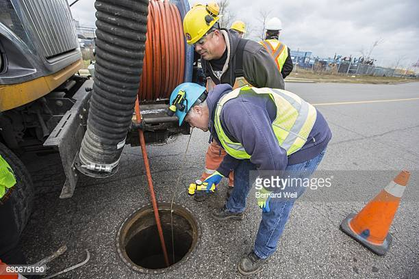 TORONTO ON NOVEMBER 29 Stanley Cooper and Gary Burger with Toronto Water look into a man hole as a high pressure hose is lowered into a clogged sewer...