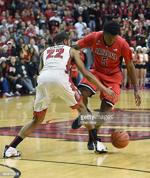 Stanley Johnson of the Arizona Wildcats loses the ball under pressure from Jelan Kendrick of the UNLV Rebels in the final seconds of their game at...