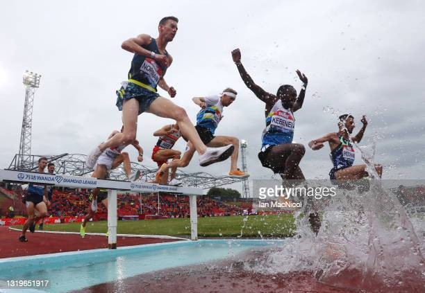 Stanley Kipkoech Kebenei of the United States and Phil Norman of Great Britain clear the water jump in the Men's 3000 metres Steeplechase during the...
