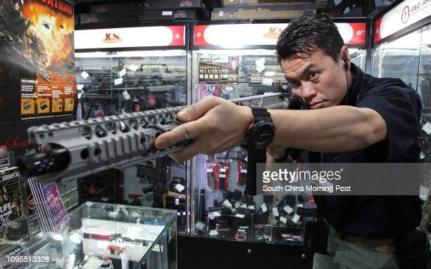 Stanley Leung shop manager of eHobby Asia poses for a photograph with an airsoft gun in Cheung Sha Wan 25FEB15 [2015 FEATURES LIFE]