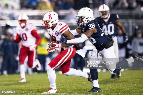 Stanley Morgan Jr #8 of the Nebraska Cornhuskers is brought down by Lamont Wade of the Penn State Nittany Lions just prior to a hit by Troy Apke...