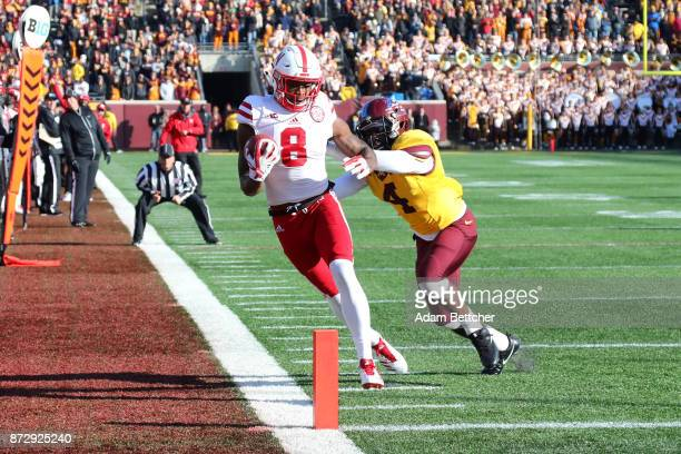 Stanley Morgan Jr #8 of the Nebraska Cornhuskers pulls in a pass while Adekunle Ayinde of the Minnesota Golden Gophers attempts the block in the...