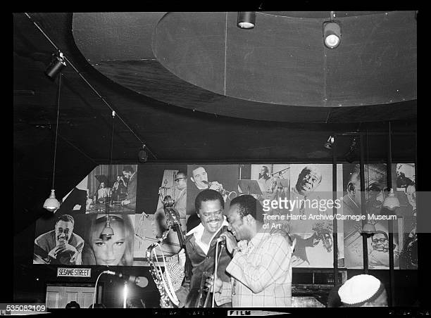 Stanley Turrentine with saxophone and Walt Harper at microphone in Walt Harper's Attic with large portraits of musicians and sign reading 'Sesame...