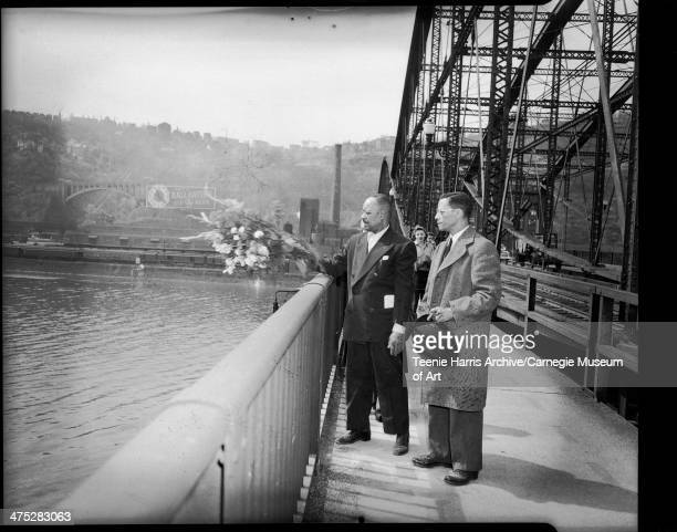 Stanley Williams throwing flowers into Monongahela River from Smithfield Street bridge in honor of his brother Charles McDonald Williams with Thomas...