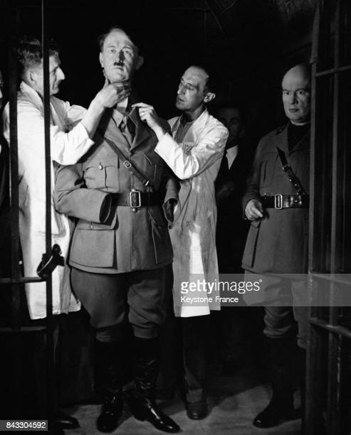 Stanley Wismark et George Hopkins assemblent la tête représentant Adolf Hitler sur le reste de son corps dans la Chambre des Horreurs à côté d'un...