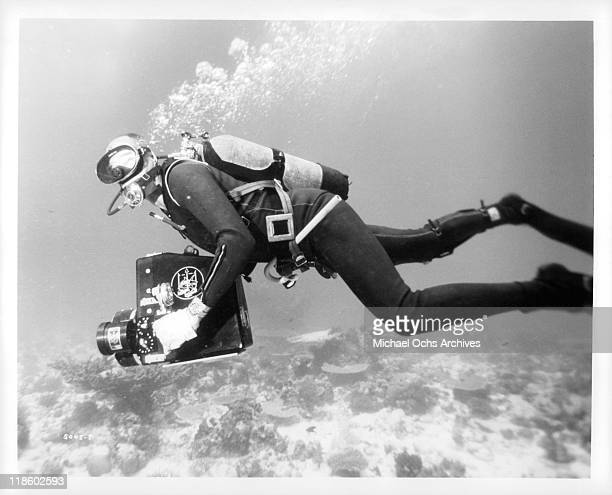 Stanton Waterman underwater with camera in a scene from the film 'Blue Water, White Death', 1971.