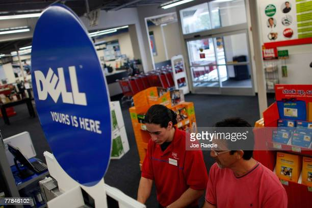 Staples sales associate Paul Capon helps Jorge Bascha look at a Dell computer on sale at a store November 11 2007 in Miami Florida Dell Inc today...