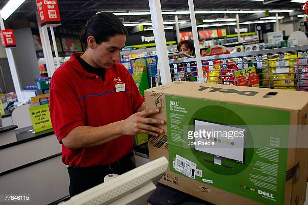 Staples sales associate Paul Capon rings up the sale of a Dell computer monitor November 11 2007 in Miami Florida Dell Inc today began selling...