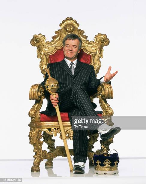 Star and ex Radio One DJ and winner of I'm A Celebrity Get Me Out Of Here, Tony Blackburn, sitting on a thrown, circa 2002.